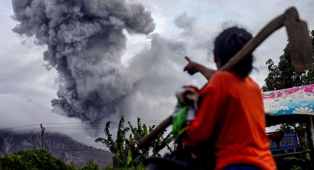 Pequeno morador rural observa vulcão Sinabung, Indonésia