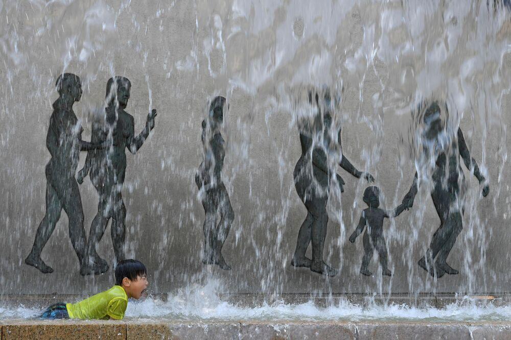 Menino toma banho em chafariz em Tóquio, Japão