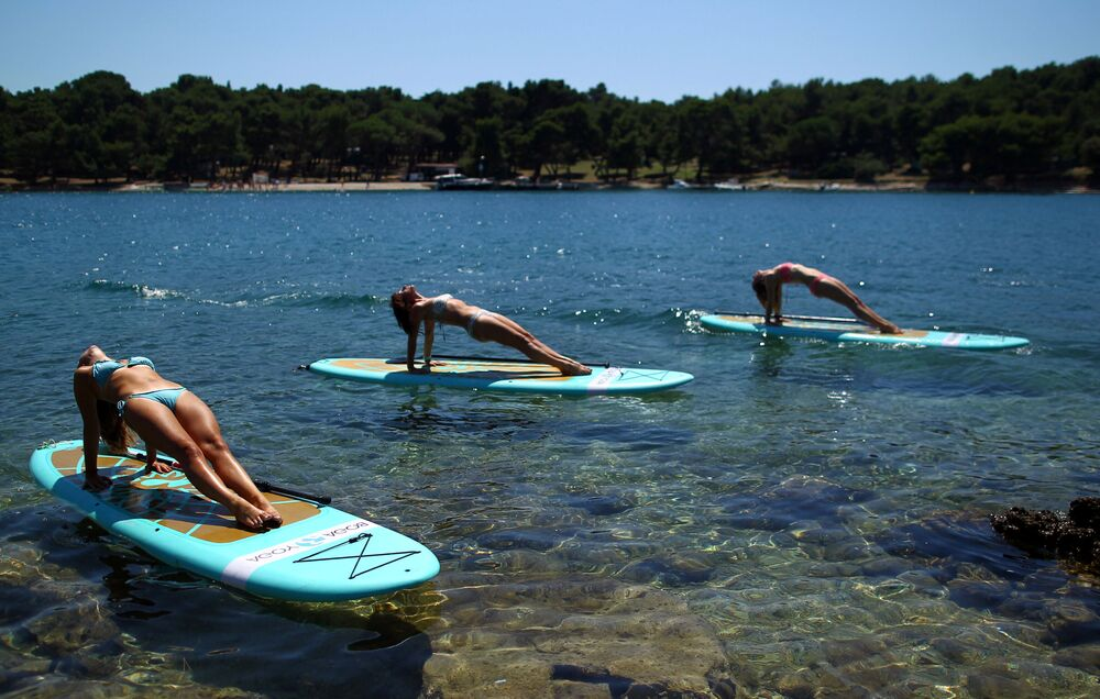 Meninas fazem ioga na costa do mar Adriático, Croácia