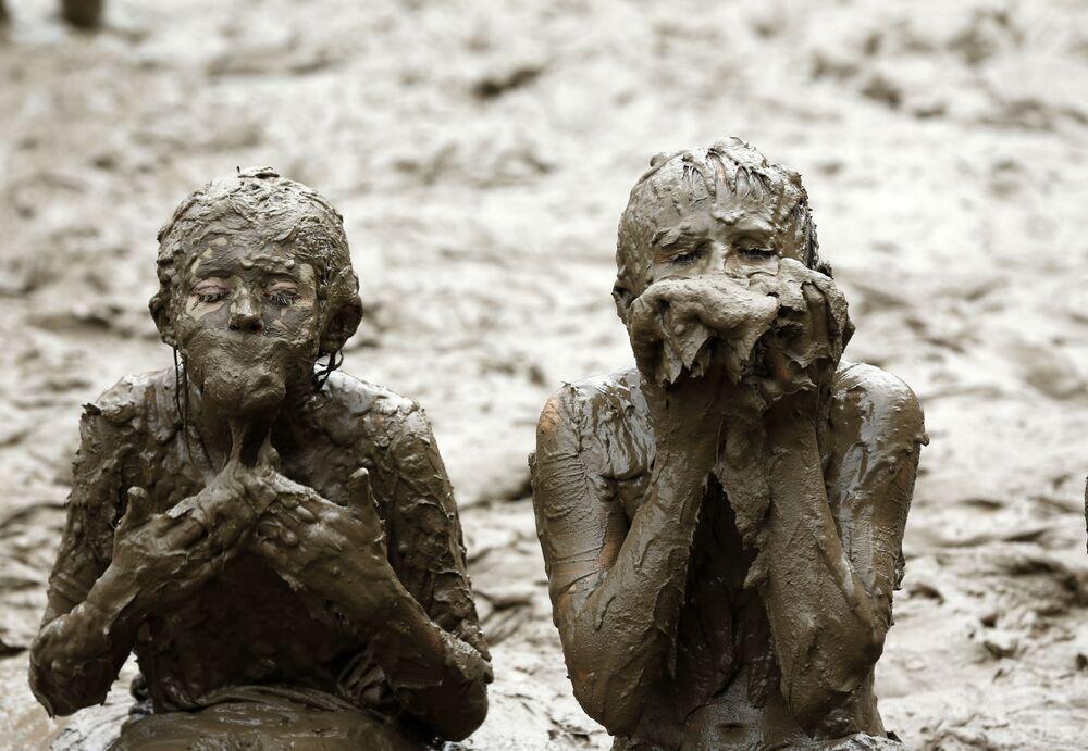 Crianças brincam com lama no Dia da Lama, Michigan, EUA