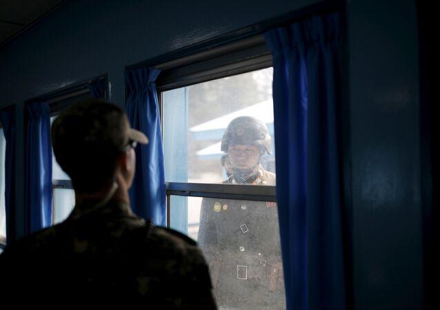 Soldados norte e sul-coreano se olham através de uma janela de uma sala no Edifício da Conferência da Comissão de Armistidade Militar do Comando das Nações Unidas na aldeia da trégua de Panmunjom (Foto de arquivo)