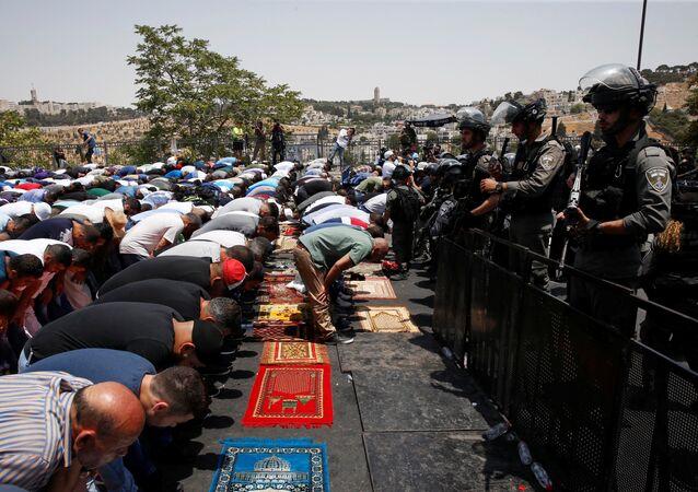 Palestinos religiosos rezam na rua em Jerusalém, vigiados pela polícia de Israel, em 21 de julho de 2017