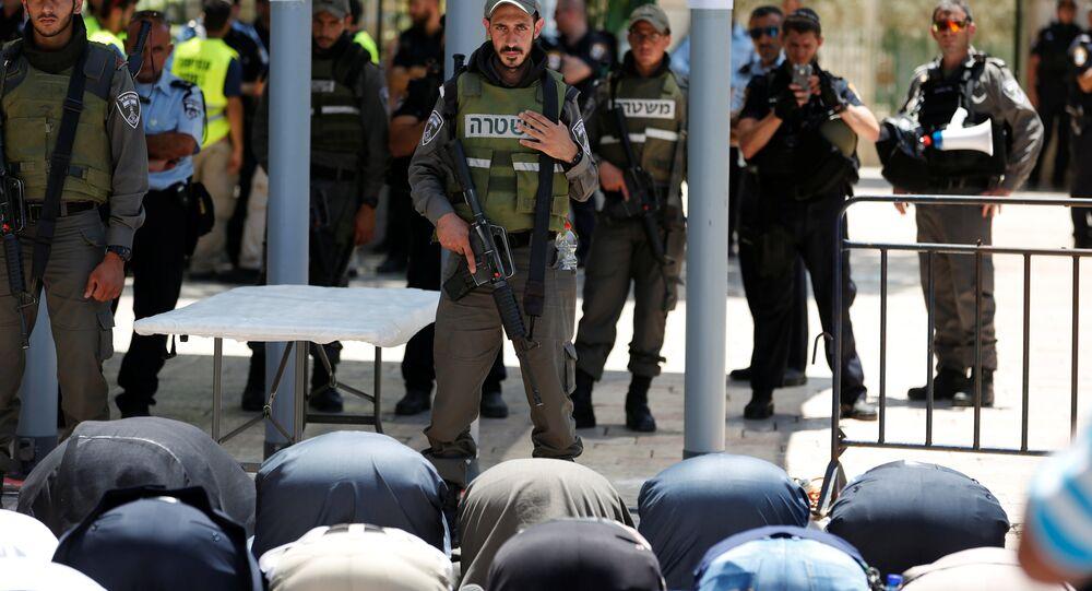 Palestinos rezam enquanto no Monte do Templo enquanto soldados israelenses observam