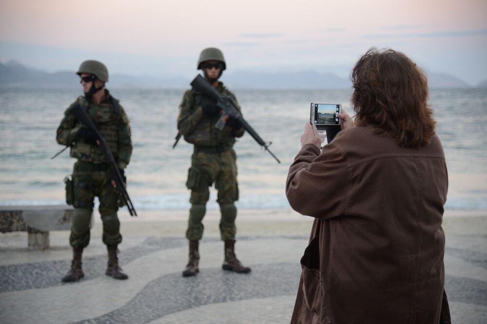 Pedestrem tiram fotos de militares que ocupam praia de Copacana em operação das Forças Armadas no Rio