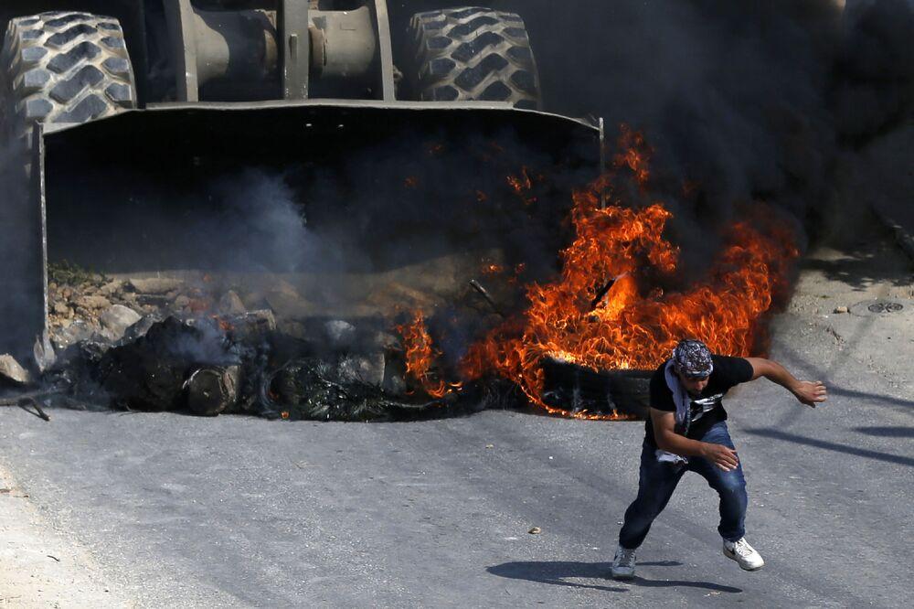 Um manifestante palestino foge de um buldózer do exército israelense durante os confrontos na aldeia de Kobar, a oeste de Ramalá