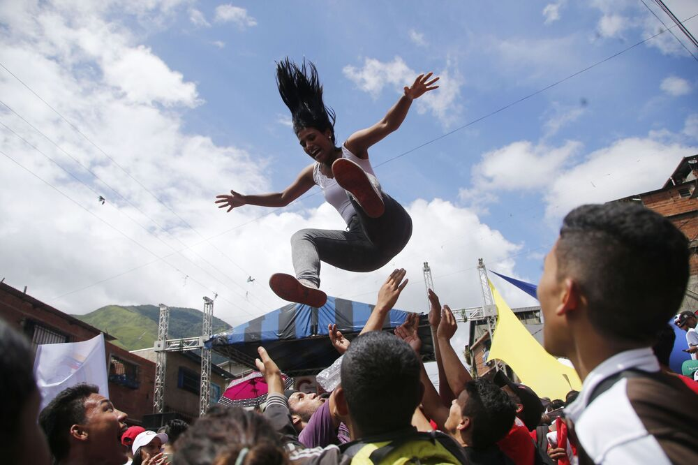 A multidão lança uma mulher ao ar durante um comício eleitoral dos candidatos à Assembleia Constituinte de Caracas, na Venezuela