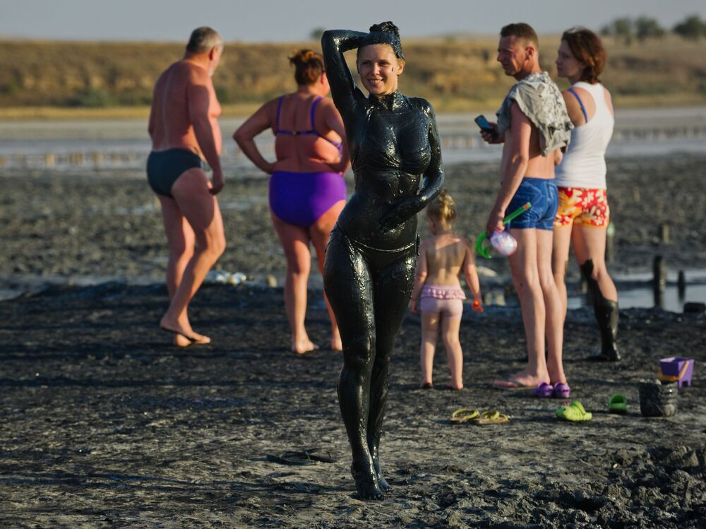 Turistas no lago de lodo medicinal Chokrakskoye, na Crimeia