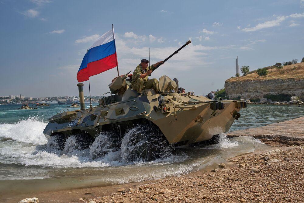 Um veículo blindado BTR-82A ultrapassa um obstáculo aquático enquanto a tripulação desembarca na costa durante o ensaio geral da parada no Dia da Marinha em Sevastopol
