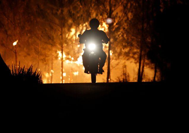 Um bombeiro anda de moto em direção oposta ao incêndio florestal na aldeia de Mação, perto de Castelo Branco, em Portugal