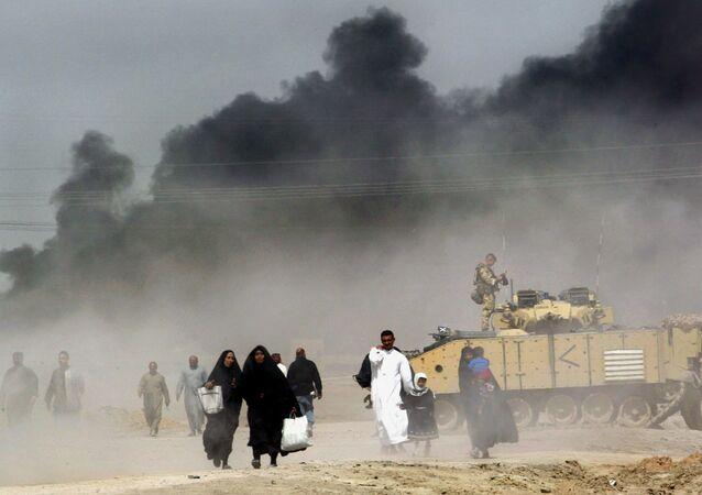 Um grupo de iraquianos fogem de Basra, sul do Iraque, passando perto de um tanque britânico, em 29 de março de 2003
