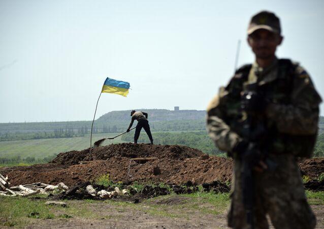 Militar ucraniano mantem sua posição, enquanto trabalhadores estão cavando trincheiras na linha da frente do confronto contra milicianos independentistas no Leste da Ucrânia em 26 de maio de 2015