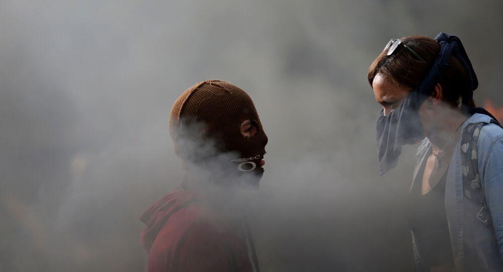 Manifestantes se olham enquanto se reúnem contra o governo do presidente da Venezuela, Nicolas Maduro, em Caracas
