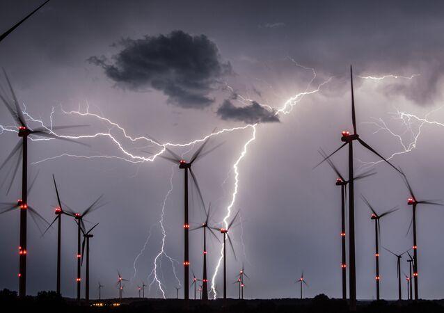 Relâmpagos cruzam o céu por cima dos moinhos de vento