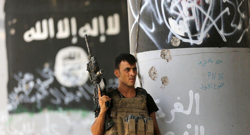 Um membro das forças anti-terroristas iraquianas realizada a sua guarda próximo a um grafite do grupo terrorista Daesh, em Fallujah, Iraque.