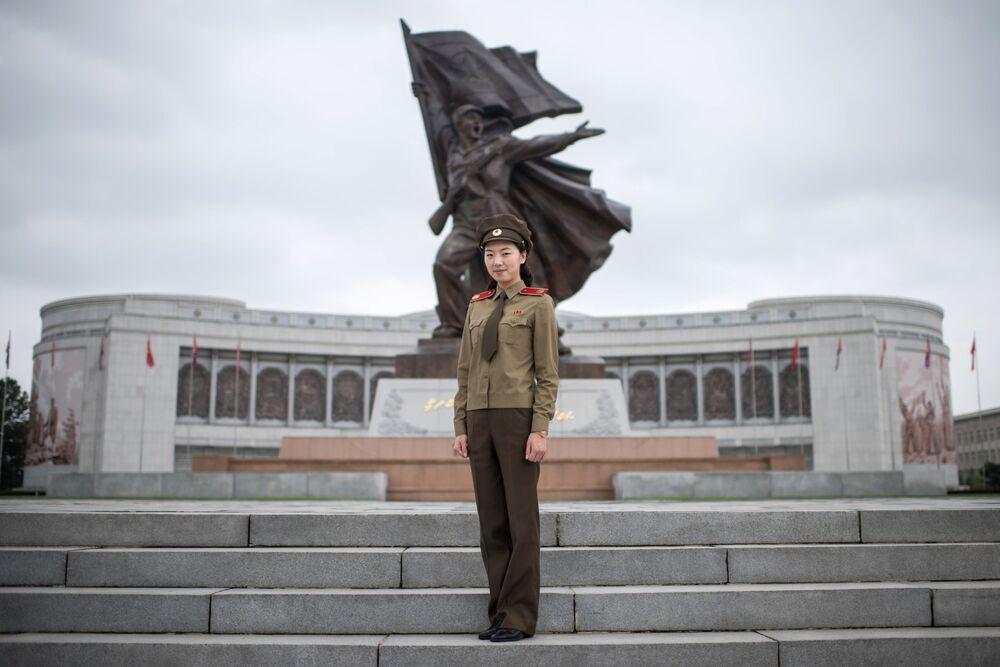 A guia e a capitã do exército norte-coreano Choe Un-Jong em frente ao Museu da Guerra em Pyongyang