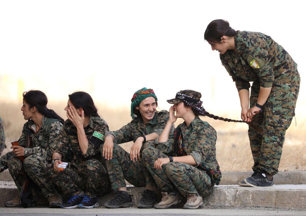 Mulheres combatentes das Forças Democráticas Sírias esperam na beira da estrada na cidade de Hasaka, no nordeste da Síria
