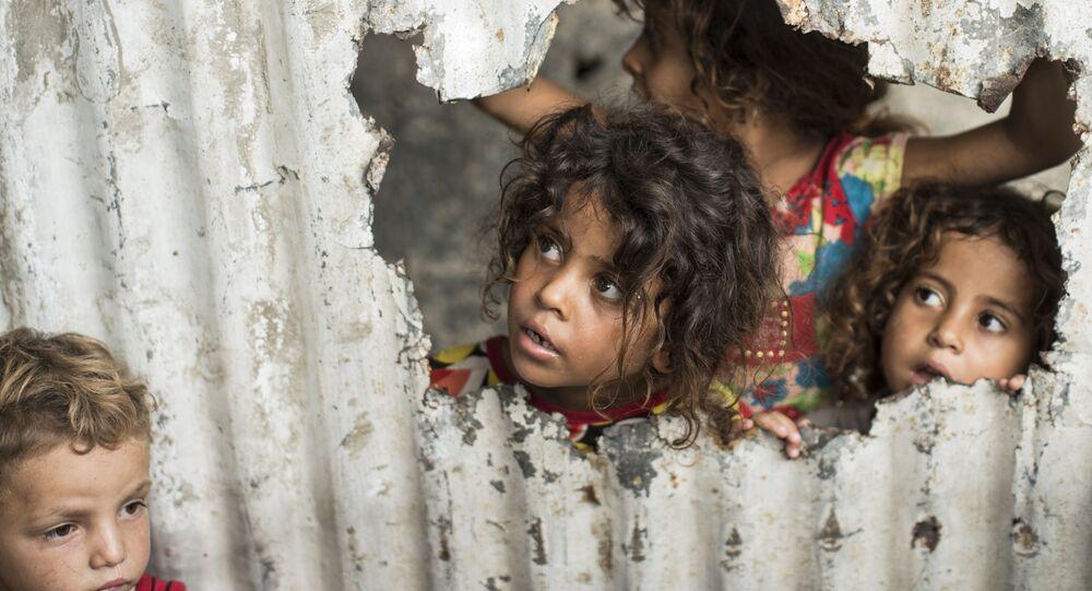 Crianças palestinas olham através de um buraco no cercado em um bairro pobre de Gaza