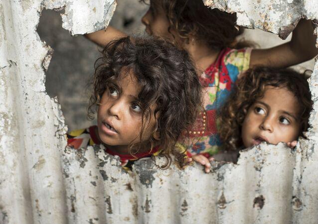Crianças palestinas olham através de um buraco no cercado em um bairro pobre de Gaza (arquivo)