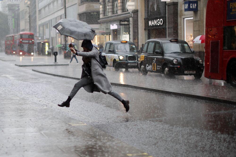 Uma pedestre pula para atravessar a rua durante um aguaceiro em Londres