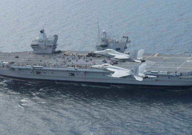 Os aviões ameicanos F/A-18E e F/A-18F Super Hornets sobrevoam o porta-aviões britânico HMS Queen Elizabeth durante as manobras Saxon Warrior no Atlântico, em 5 de agosot de 2017