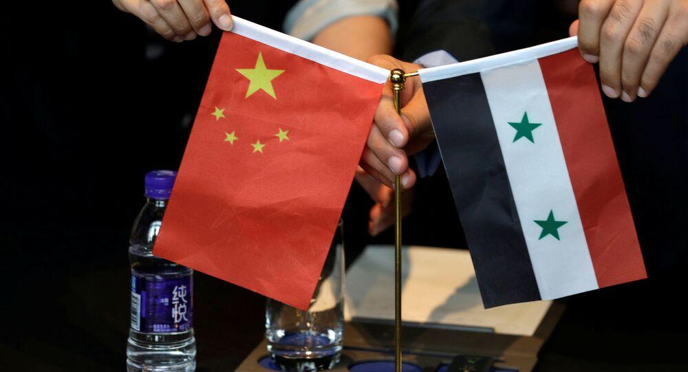 Empresários sírios e chineses exibem bandeiras dos dois países durante encontro em Pequim para discutir projetos de reconstrução da Síria (arquivo)