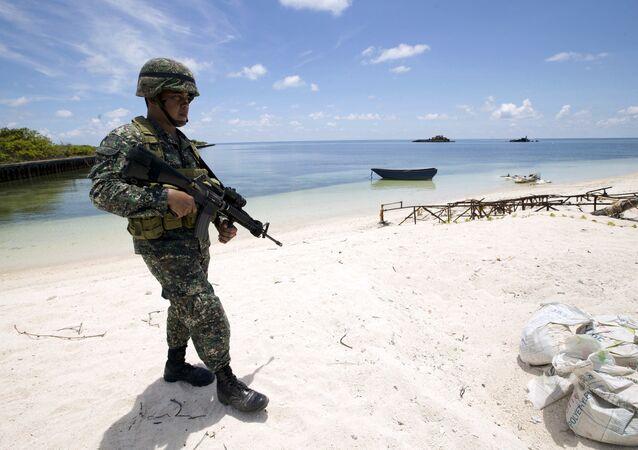 Um soldado filipino patrulhando a costa da ilha de Thitu, no arquipélago de Spratly, no mar do Sul da China (foto de arquivo)