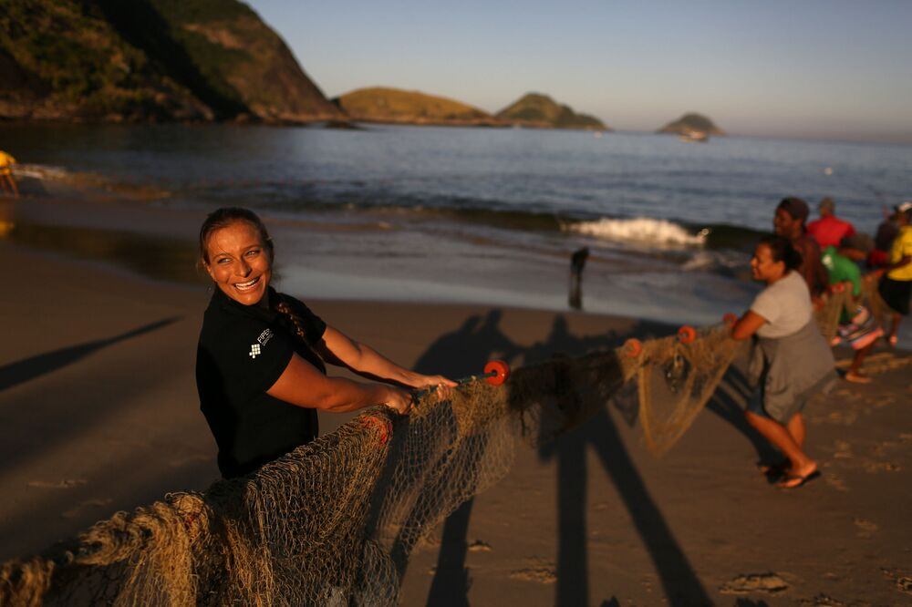 Sereia e instrutora de mergulho, Luciana Fuzetti ajuda pescadores a puxar uma rede em uma praia de Niterói, Brasil, em 13 de julho de 2017