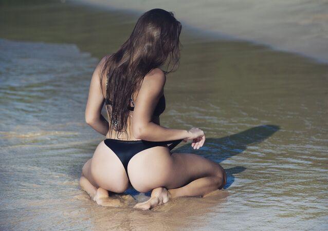 Mulher em uma praia (imagem referencial)