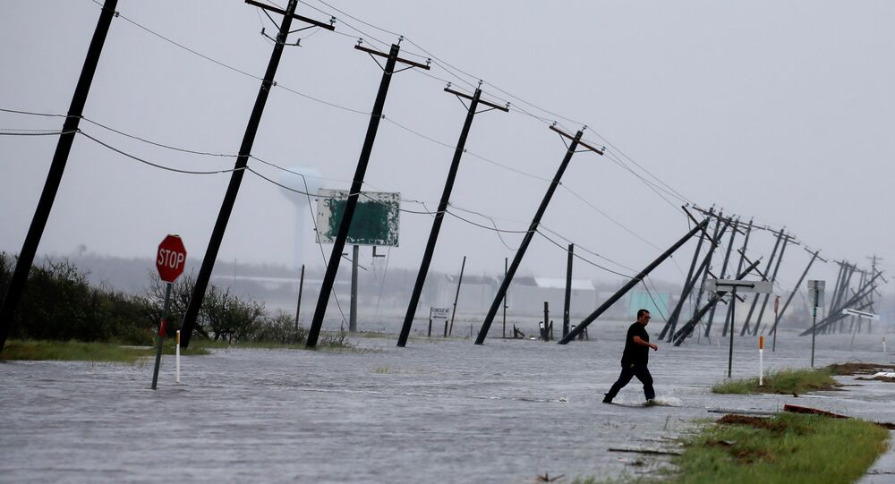 A man walks through floods waters and onto the main road after surveying his property which was hit by Hurricane Harvey in Rockport, Texas, U.S. August 26, 2017.