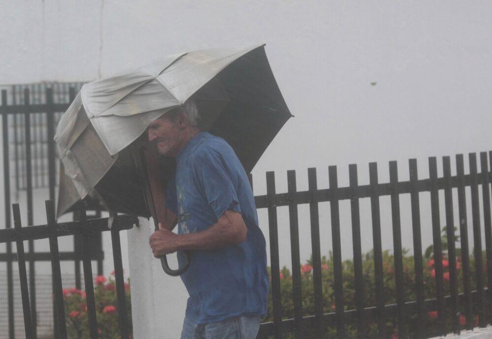 Homem com guarda-chuvas tenta resistir à força do furacão Irma, em Porto Rico