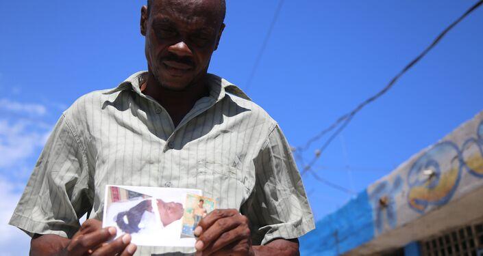 O vendedor Ilphim Jean Gilles (51 anos) mostra a foto da filha Woodeline, morta em 2013 aos 24 anos vítima de cólera: Ela era minha primogênita, tudo pra mim. Os soldados da ONU levaram embora minha esperança.
