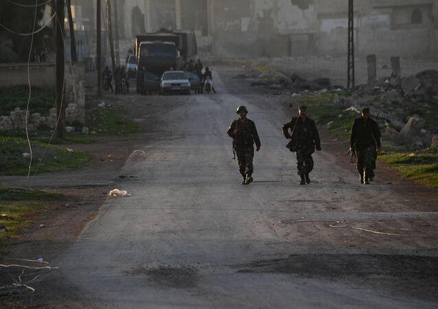 Soldados sírios são vistos no povoado Majdal, ao norte da cidade de Hama, na Síria