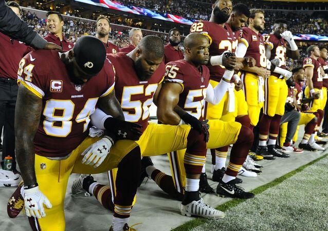 Jogadores do Washington Redskins (NFL) ajoelham-se para o hino nacional.