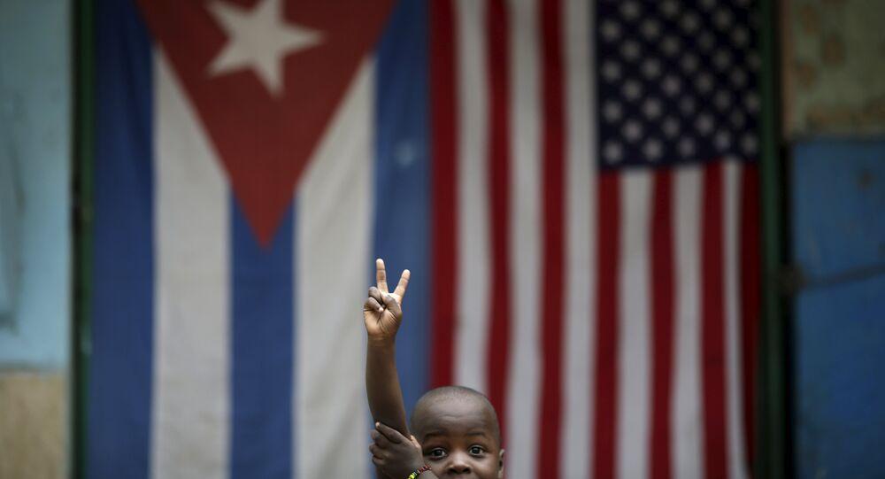 Eric, de 3 anos, faz sinal de paz e amor enquanto posa para uma fotografia em frente às bandeiras de Cuba e dos EUA em Havana, 25 de março de 2016