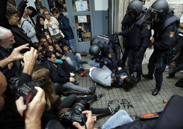 Polícia espanhola imobiliza várias pessoas perto de seção eleitoral em Barcelona, 1 de outubro de 2017, no dia do refendo pela independência, declarado ilegal por Madri