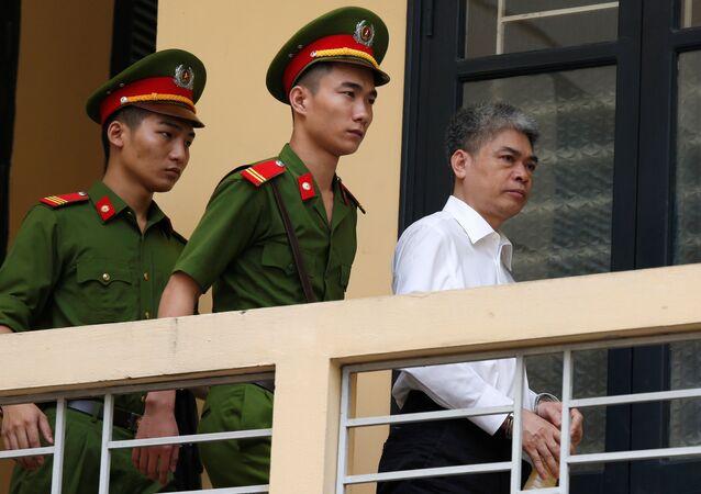 O ex-presidente do PetroVietnam (PVN), Nguyen Xuan Son, é acompanhado pela polícia enquanto sai do tribunal após a sessão de veredito em Hanói