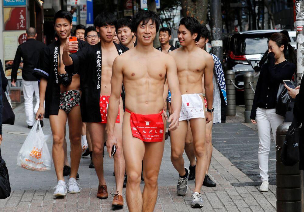 Japoneses vestidos de trajes nacionais fundoshi saem às ruas para recolher lixo