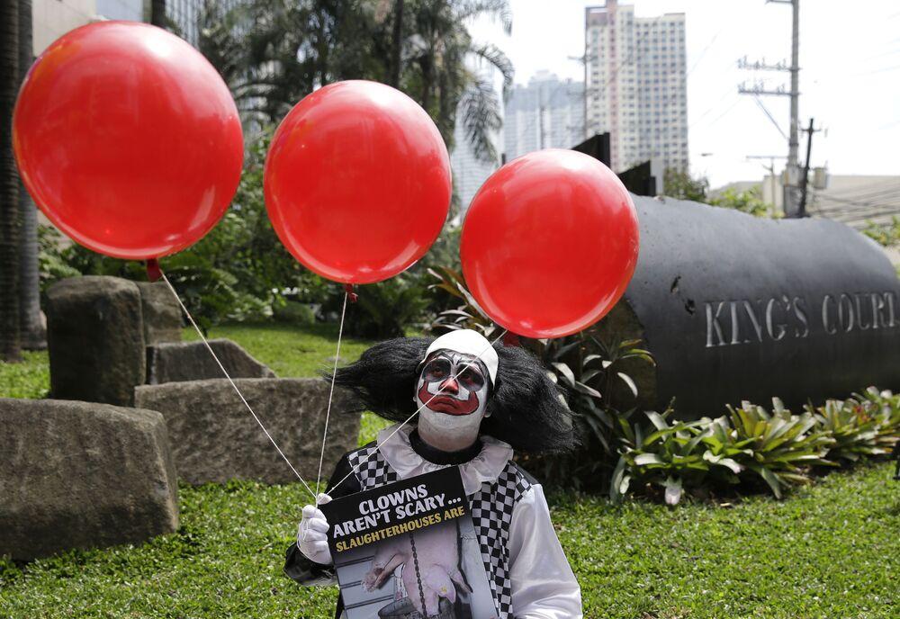 Homem vestido de palhaço durante demonstração de vegetarianos em Manila, Filipinas