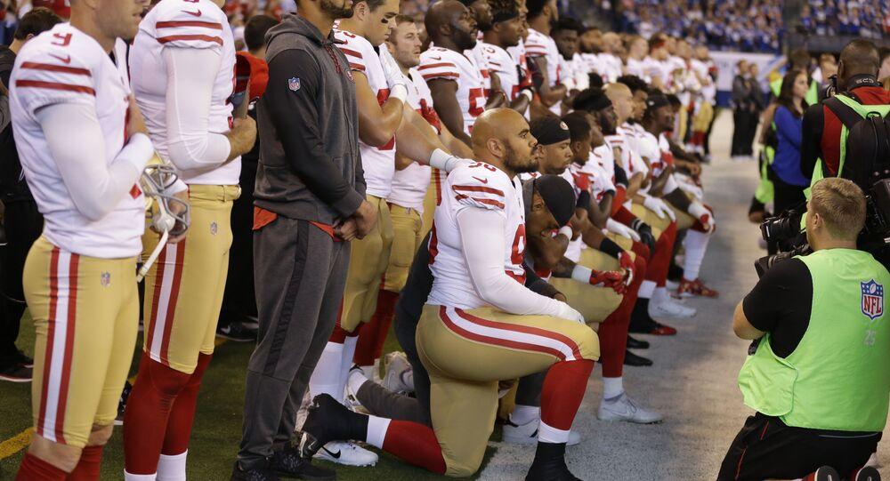 Jogadores do San Francisco 49ers (NFL) ajoelham-se para o hino nacional.
