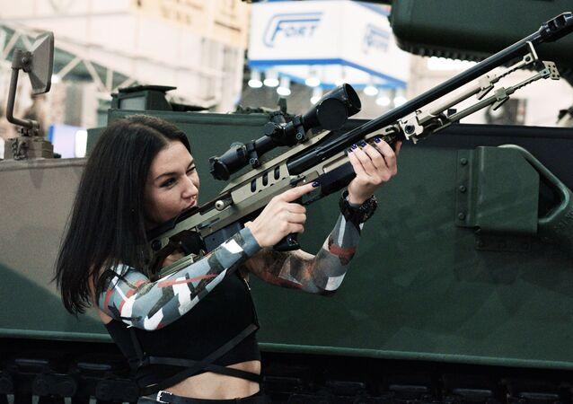 Moça examina um fuzil durante a exposição Armas e Segurança 2017 em Kiev
