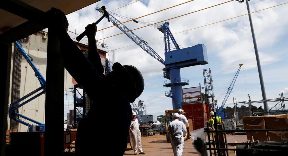 Trabalhador usando martelo perto da saída da embarcação HMS Queen Elizabeth