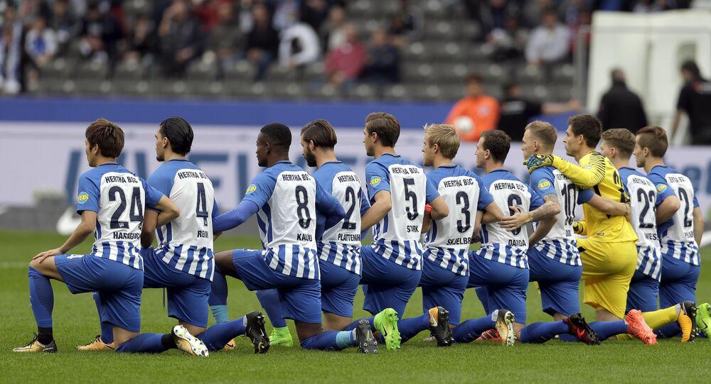 Jogadores do Hertha BSC Berlin ficam de joelhos durante jogo da Bundesliga