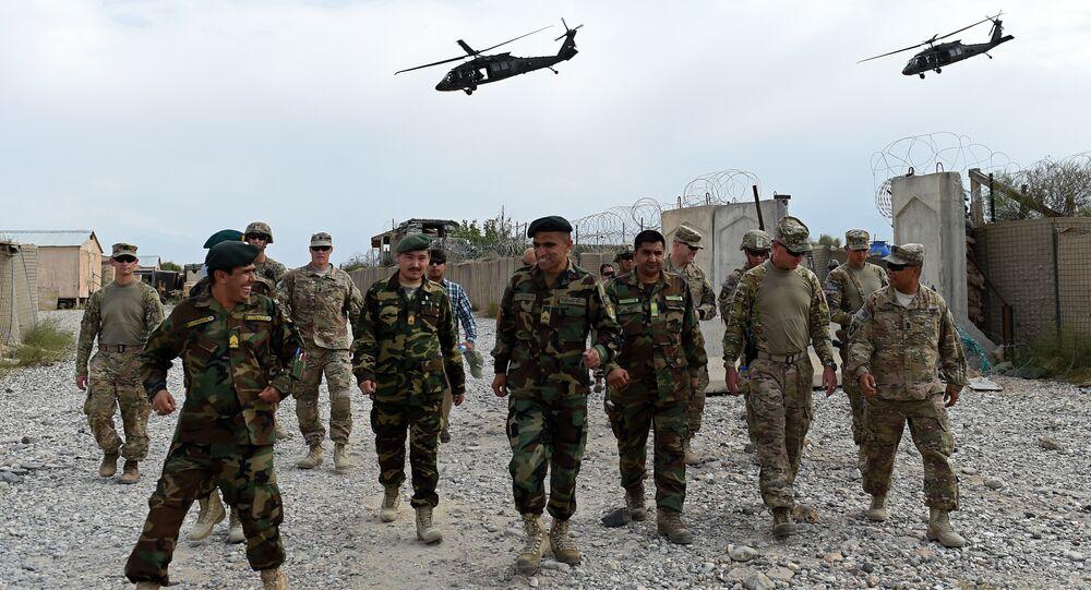 Soldados norte-americanos e afegãos andam abaixo dos helicópteros da OTAN