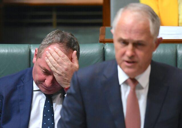 O vice-primeiro-ministro australiano, Barnaby Joyce, preocupado enquanto se senta atrás do primeiro-ministro australiano, Malcolm Turnbull, na Câmara dos Deputados de Canberra