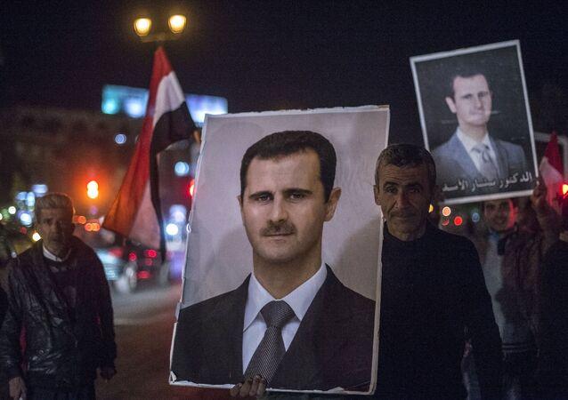 Жители Дамаска держат портреты сирийского президента Башара Асада во время встречи военнослужащих Сирийской арабской армии, участвовавших в снятии блокады с авиабазы Квейрис в провинции Алеппо