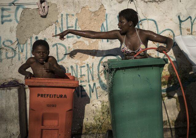 Mulher e criança tomam banho em contentores para lixo na favela da Mangueira, Rio de Janeiro