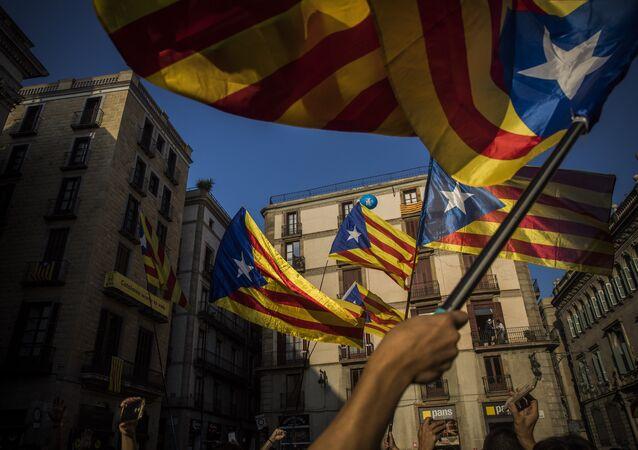 Populares com bandeiras da Catalunha durante discurso do líder local Carles Puigdemont em Barcelona