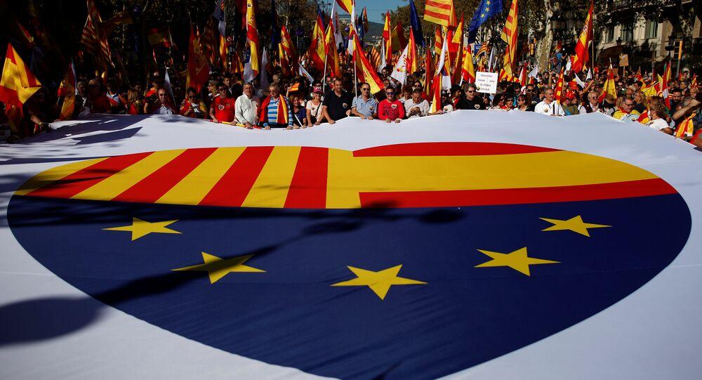 Apoiadores da Espanha unida seguram cartaz gigante com bandeiras da Catalunha, Espanha e União Europeia, Barcelona, 29 de outubro de 2017