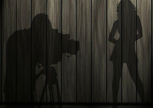 Sombras de um fotógrafo e uma modelo (imagem ilustrativa)