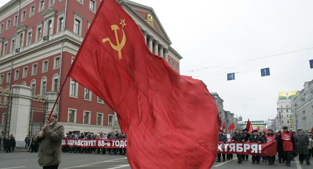 Apoiadores do comunismo carregam bandeiras da União Soviética declarando no aniversário de 88 anos da Revolução de Outubro